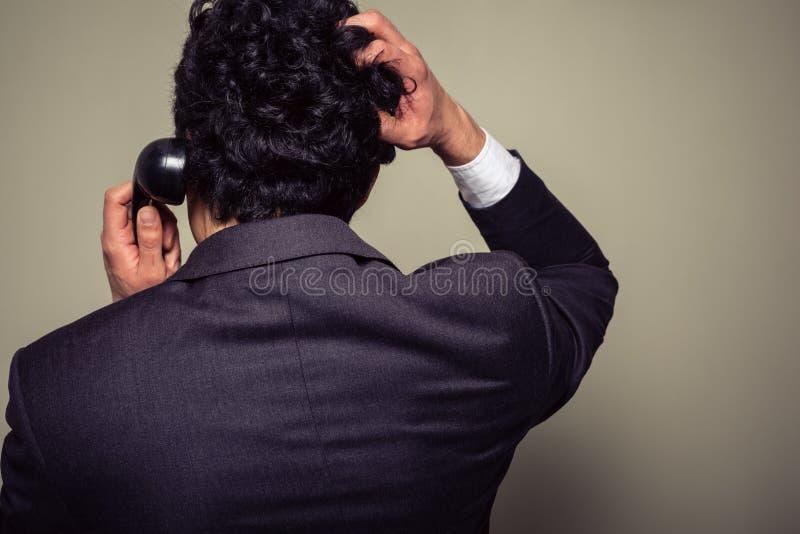 Homem de negócios confuso que risca sua cabeça fotografia de stock royalty free