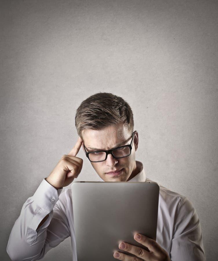 Homem de negócios confuso que usa uma tabuleta imagem de stock