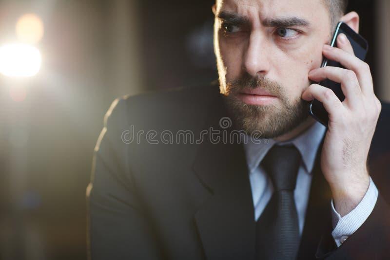 Homem de negócios confuso Speaking por Smartphone imagens de stock royalty free