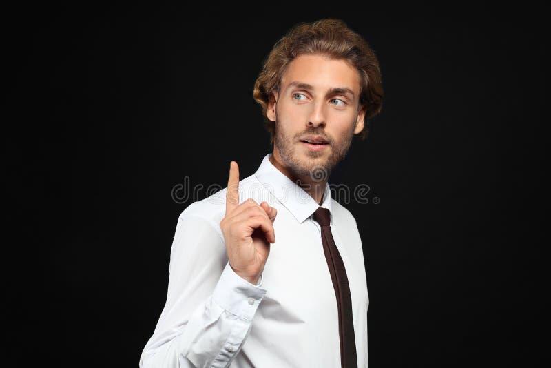 Homem de negócios considerável com o indicador aumentado no fundo preto imagens de stock royalty free