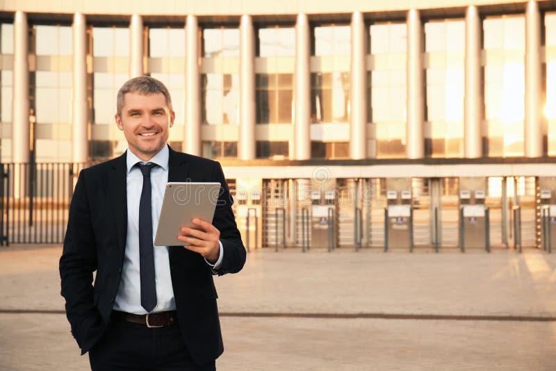 Homem de negócios considerável com PC da tabuleta fora fotografia de stock royalty free