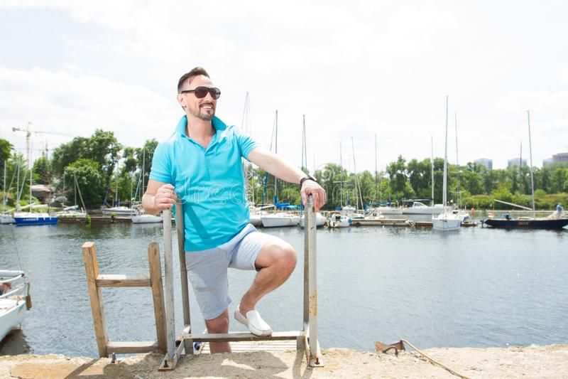 Homem de negócios considerável em férias com os iate no fundo da doca Ostente o homem nos óculos de sol que laddering acima no ba fotografia de stock