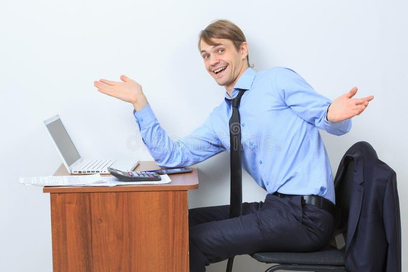 Homem de negócios considerável feliz novo em seu portátil fotografia de stock royalty free