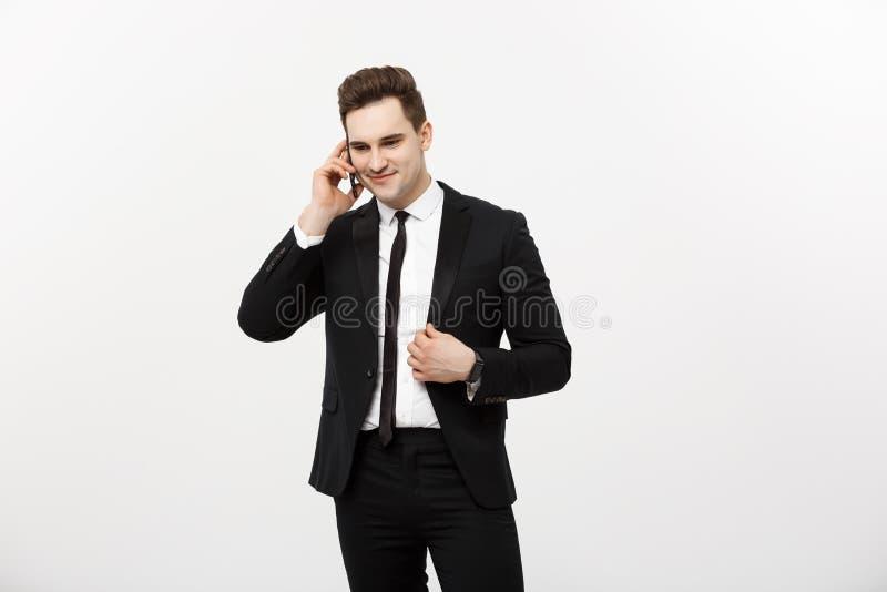 Homem de negócios considerável no terno que fala no telefone sobre o fundo branco isolado imagens de stock royalty free
