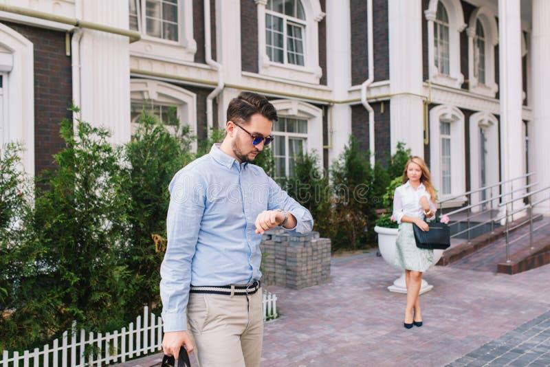 Homem de negócios considerável nos óculos de sol que olham o relógio na rua A menina loura elegante bonita está esperando-o sobre foto de stock