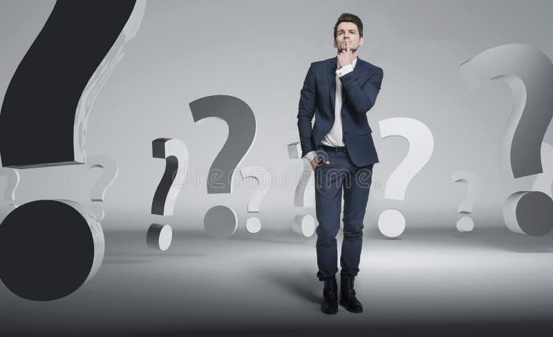Homem de negócios considerável novo entre pontos de interrogação imagens de stock royalty free