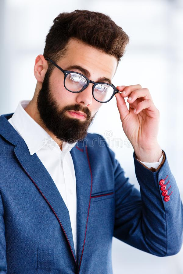 Homem de negócios considerável novo Posing At Workplace fotografia de stock royalty free