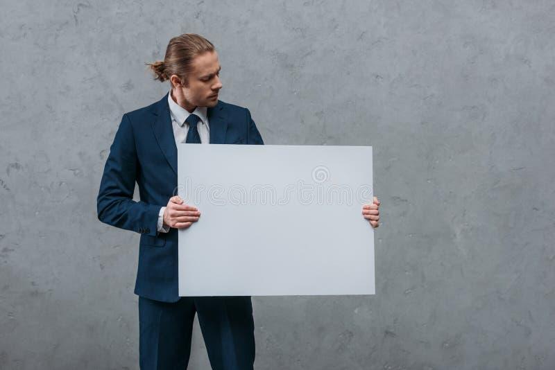 homem de negócios considerável novo que guarda a placa vazia na frente de imagem de stock