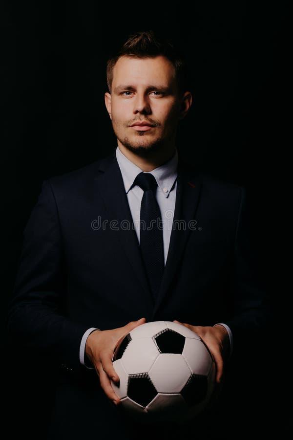 Homem de negócios considerável novo que guarda um futebol no estúdio preto do fundo imagens de stock