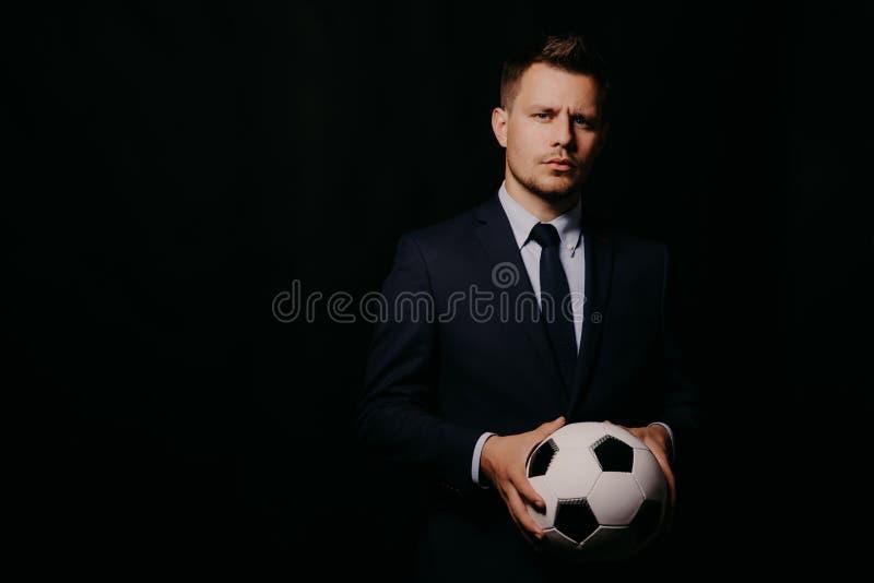 Homem de negócios considerável novo que guarda um futebol no estúdio preto do fundo foto de stock