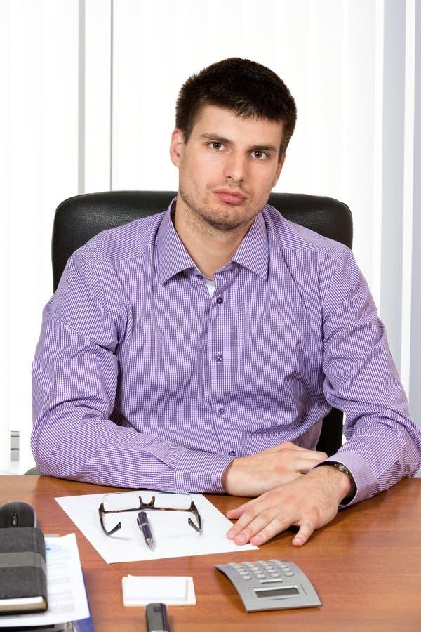 Homem de negócios considerável novo que senta-se em sua mesa fotos de stock royalty free