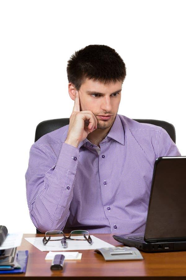 Homem de negócios considerável novo que trabalha no portátil fotografia de stock