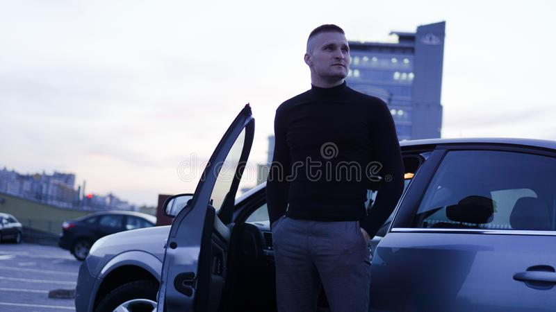 Homem de negócios considerável perto do carro na cidade foto de stock