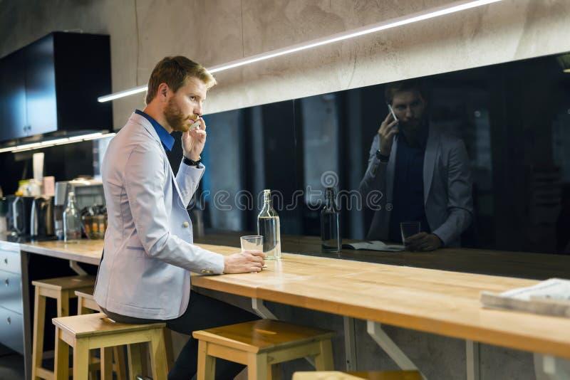 Homem de negócios considerável que bebe e que usa o telefone imagens de stock