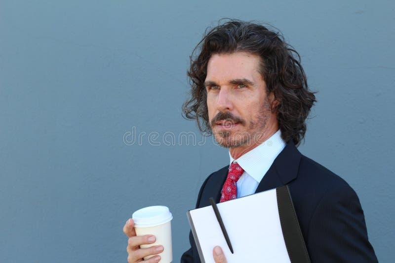 Homem de negócios considerável que guarda um dobrador e para ir copo do café ou de chá que olha afastado imagem de stock