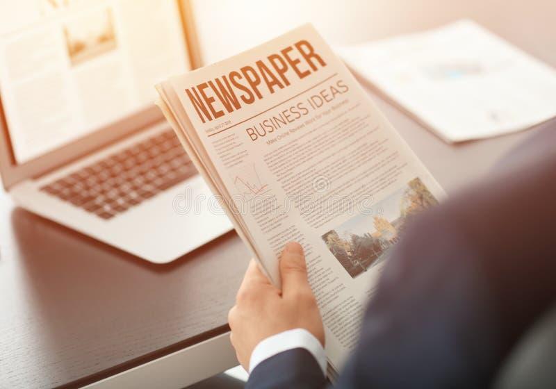 Homem de negócios considerável que lê o jornal financeiro no escritório imagens de stock