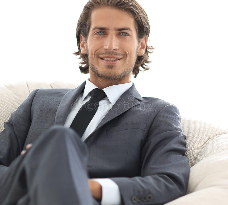 Homem de negócios considerável que senta-se em uma grande poltrona acolhedor imagens de stock