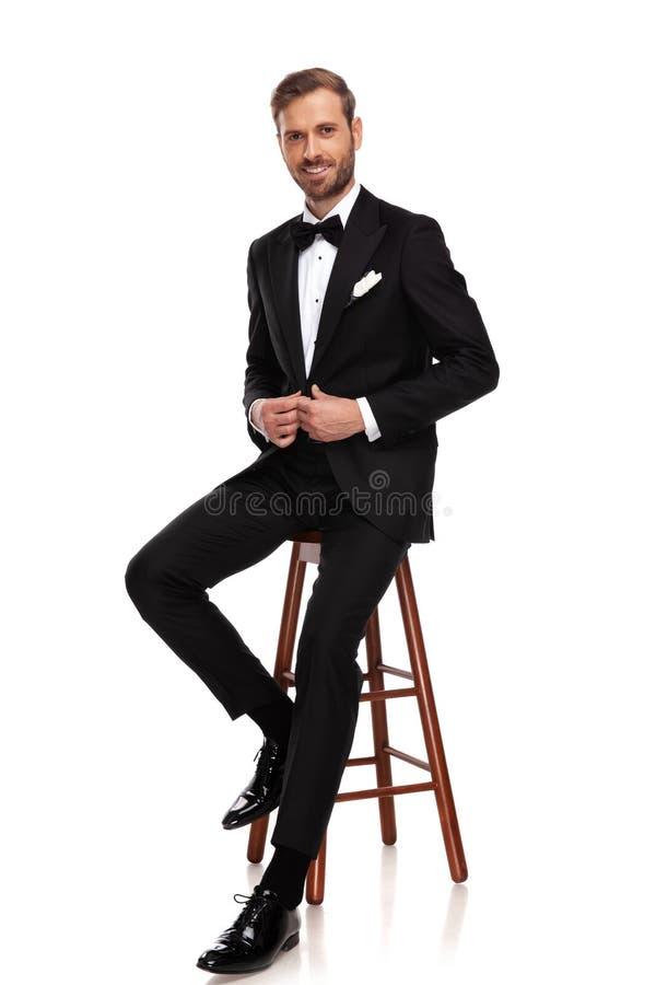 Homem de negócios considerável que senta-se no tamborete de madeira fotos de stock royalty free