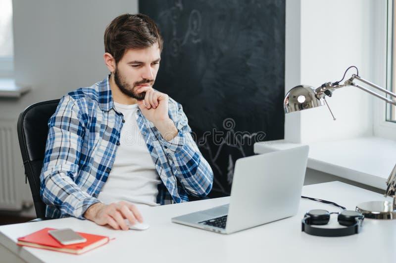Homem de negócios considerável que trabalha com o portátil no escritório foto de stock royalty free