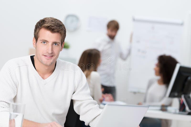 Homem de negócios considerável que trabalha em um escritório ocupado fotos de stock royalty free
