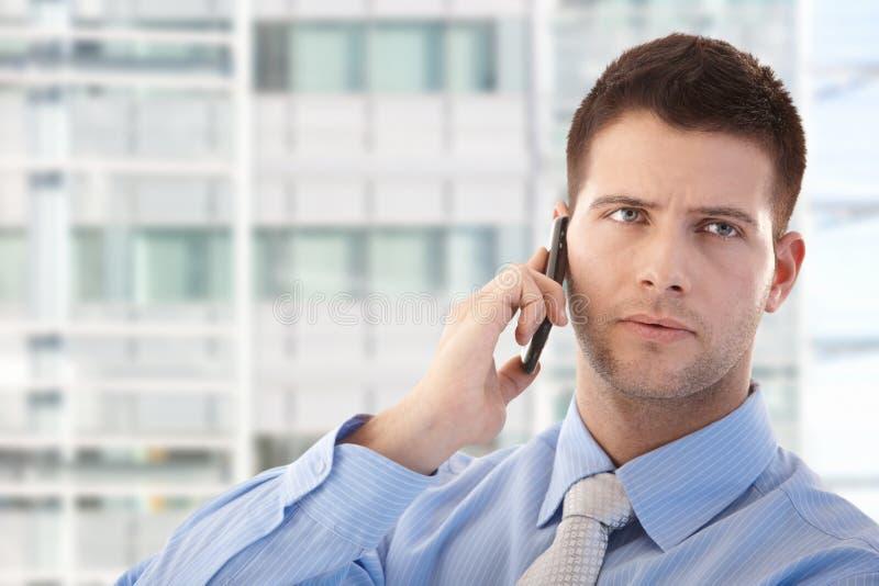 Homem de negócios considerável que usa o telefone móvel imagens de stock royalty free