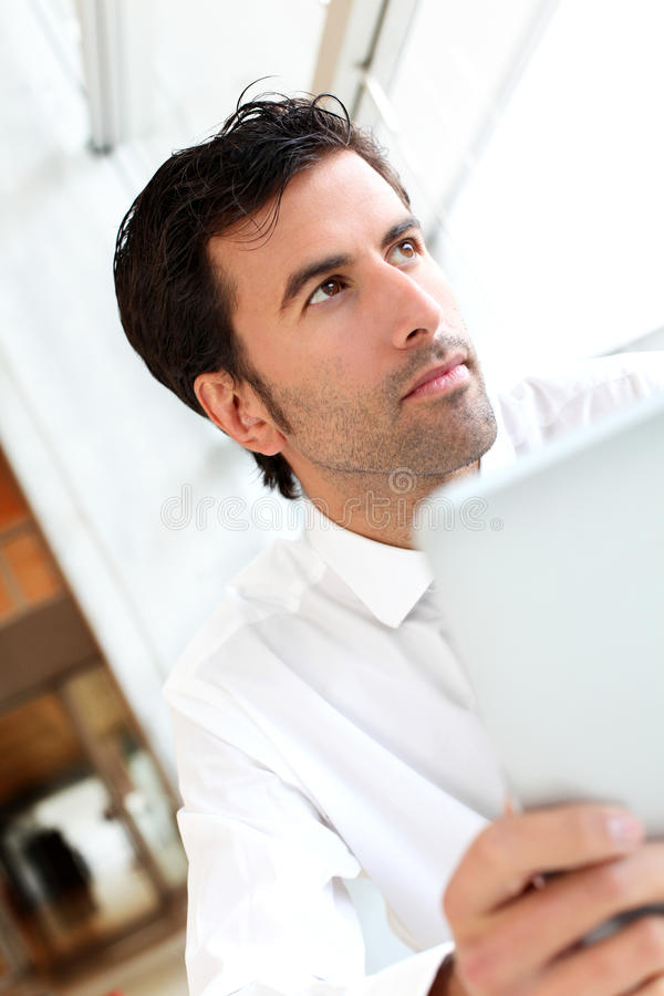 Homem de negócios considerável que usa a tabuleta foto de stock