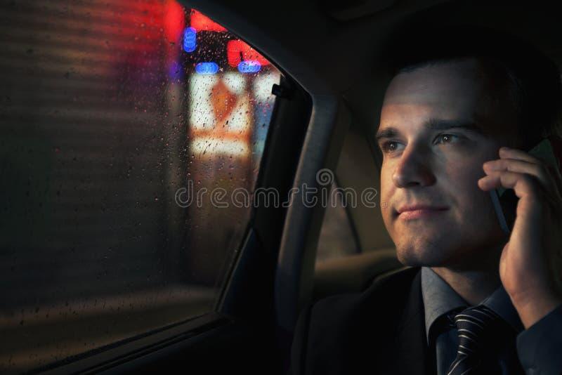 Homem de negócios contemplativo no telefone no banco traseiro de um carro que olha para fora na noite no Pequim imagens de stock