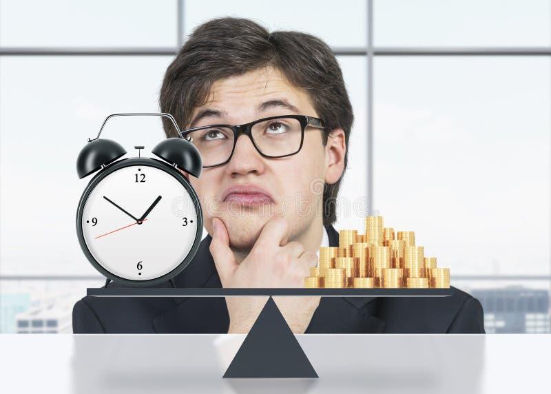 Homem de negócios contemplativo sobre o equilíbrio entre o tempo e o dinheiro É por um lado o dinheiro, no outro é um despertador foto de stock royalty free