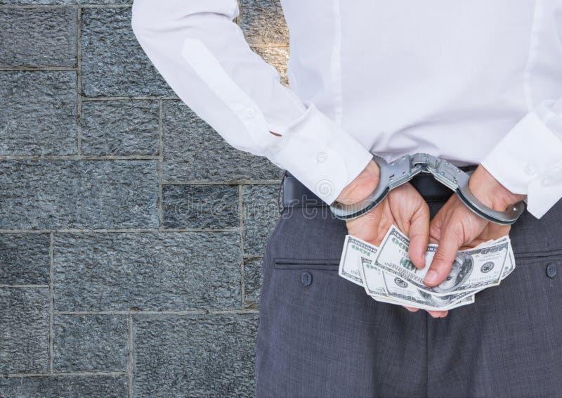 Homem de negócios corrompido nas algemas que mantêm o dinheiro contra a parede imagem de stock royalty free