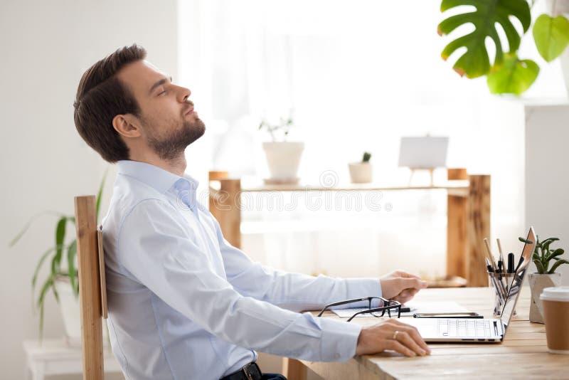 Homem de negócios da calma que toma a ruptura para relaxar o trabalho terminado no escritório imagem de stock royalty free