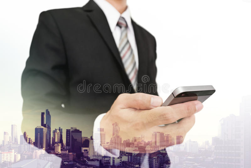 Homem de negócios da exposição dobro que usa o smartphone com fundo da opinião da cidade imagem de stock royalty free
