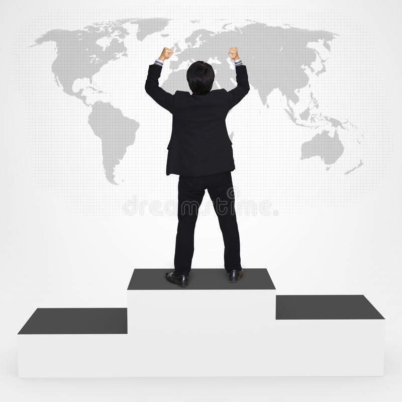 Homem de negócios da felicidade que está no pódio do vencedor foto de stock