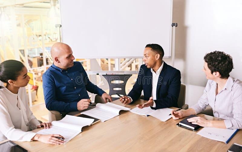 Homem de negócios da raça misturada que conduz sua equipe em sua reunião de negócios imagens de stock royalty free