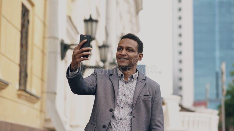 Homem de negócios da raça misturada que tem o bate-papo video em linha na conferência de negócio usando o smartphone imagem de stock royalty free