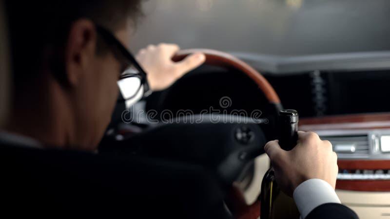 Homem de negócios da virada que senta-se no carro com garrafa de vinho, condução irresponsável, crise fotografia de stock