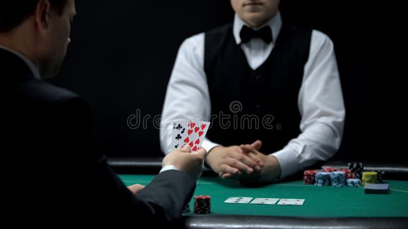 Homem de negócios da virada que tem a combinação má no pôquer, vitórias fracas dos cartões do casino da mão fotos de stock royalty free