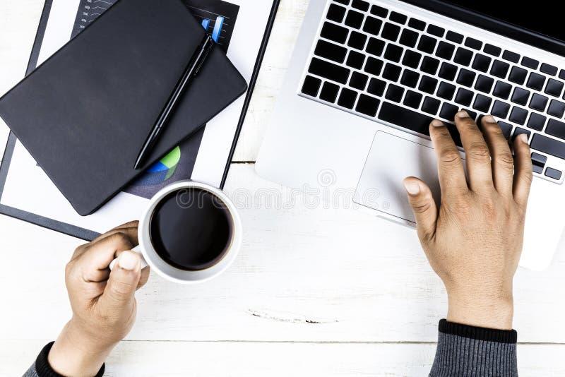 Homem de negócios da vista superior que trabalha com o local de trabalho moderno com o portátil na tabela branca, mão do homem no imagem de stock