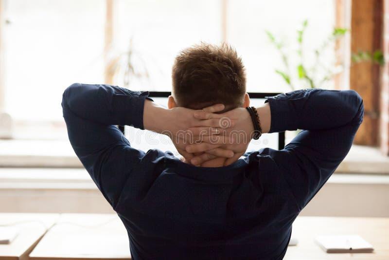 Homem de negócios da vista traseira que senta-se na cadeira que põe as mãos atrás da cabeça fotografia de stock