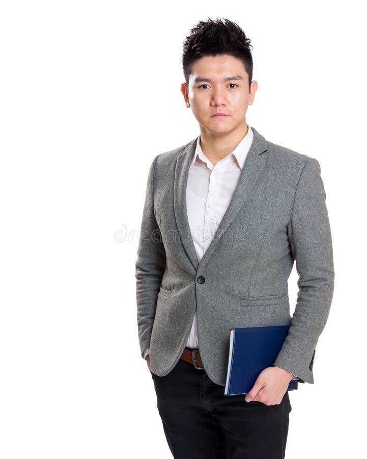 Homem de negócios de Ásia que guarda o caderno imagem de stock royalty free