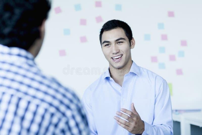 Homem de negócios de dois jovens que senta-se e que fala no escritório foto de stock royalty free