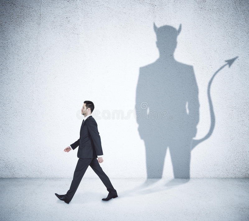 Homem de negócios de passeio com sombra do diabo foto de stock