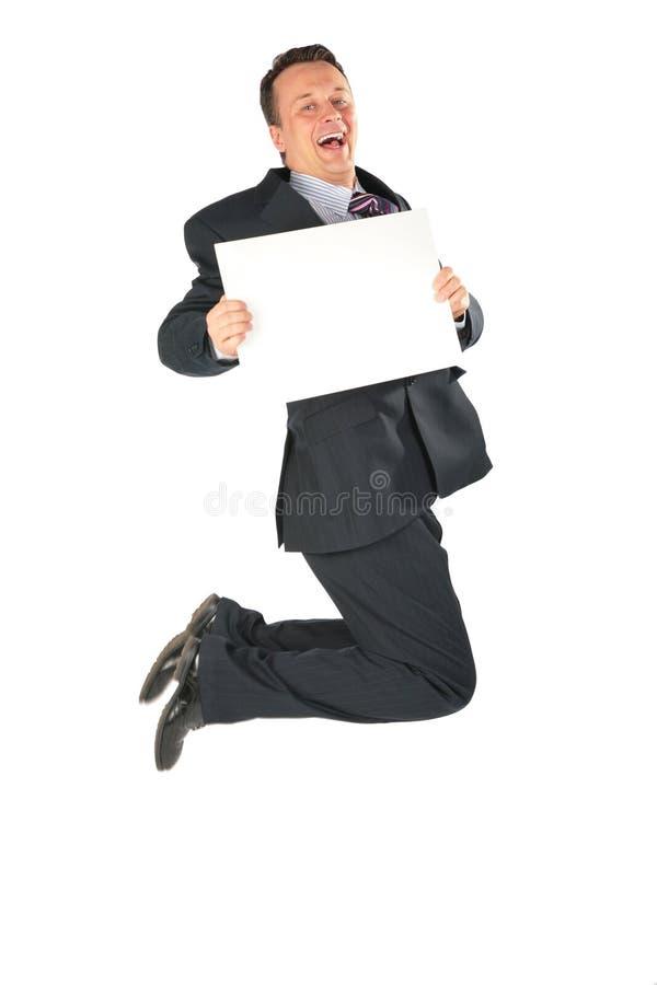 Homem de negócios de salto com papel em branco foto de stock