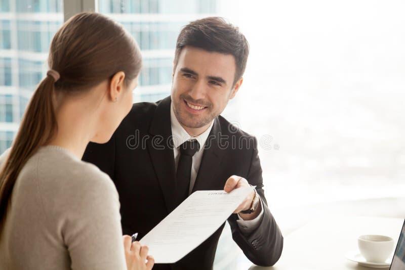 Homem de negócios de sorriso amigável que dá o contrato à mulher de negócios, o foto de stock royalty free