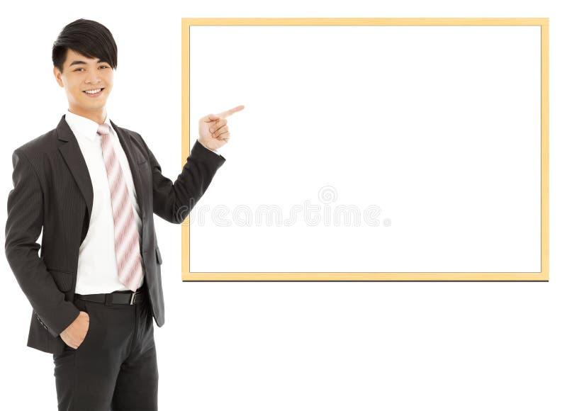 Homem de negócios de sorriso asiático que aponta a placa vazia foto de stock
