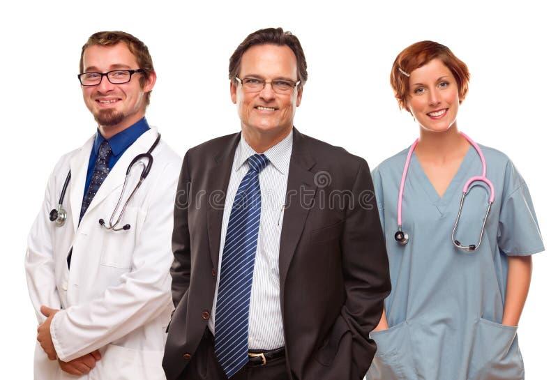 Homem de negócios de sorriso com doutores e enfermeiras imagem de stock