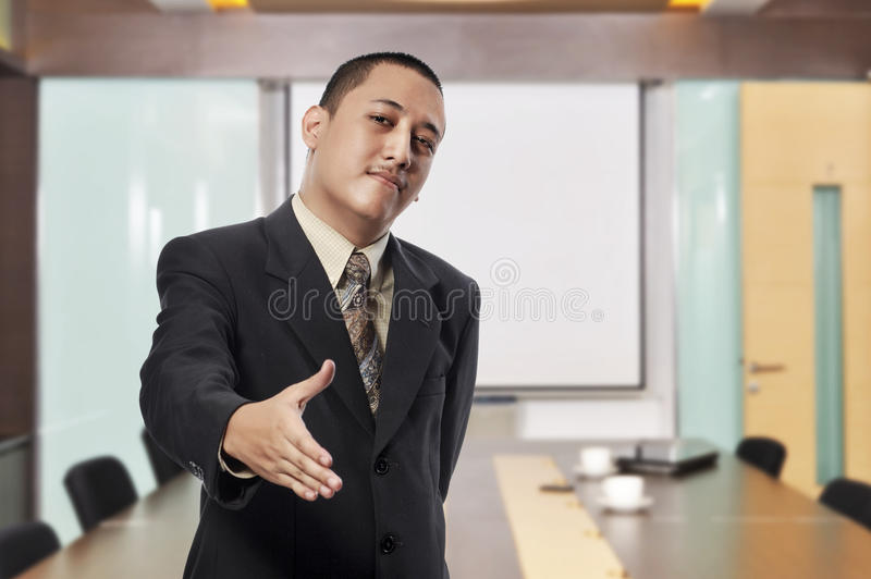 Homem de negócios de sorriso com a mão aberta pronta para entregar a agitação imagem de stock royalty free