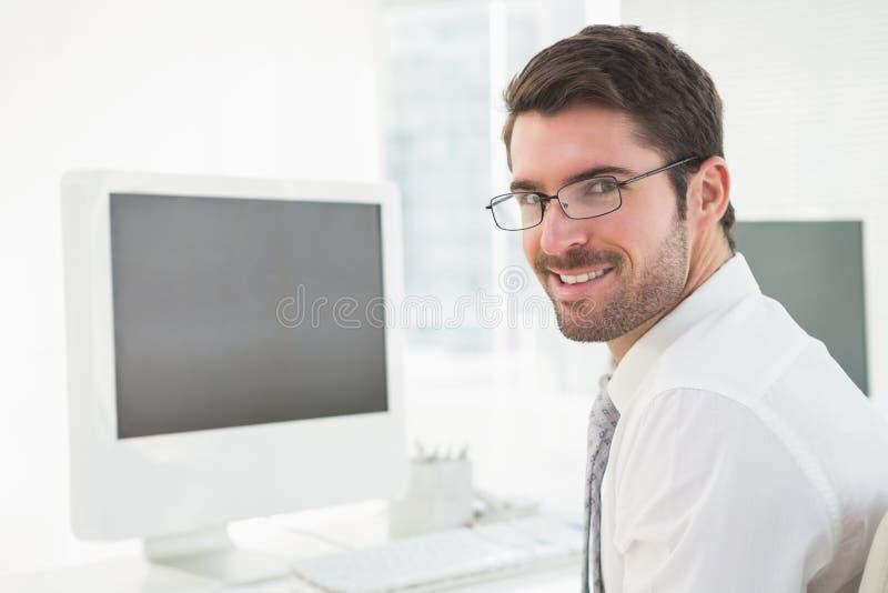 Homem de negócios de sorriso com os vidros que olham a câmera fotos de stock