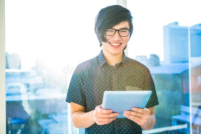 Homem de negócios de sorriso do moderno que usa a tabuleta foto de stock royalty free