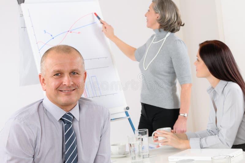 Homem de negócios de sorriso durante a reunião da equipe imagem de stock royalty free
