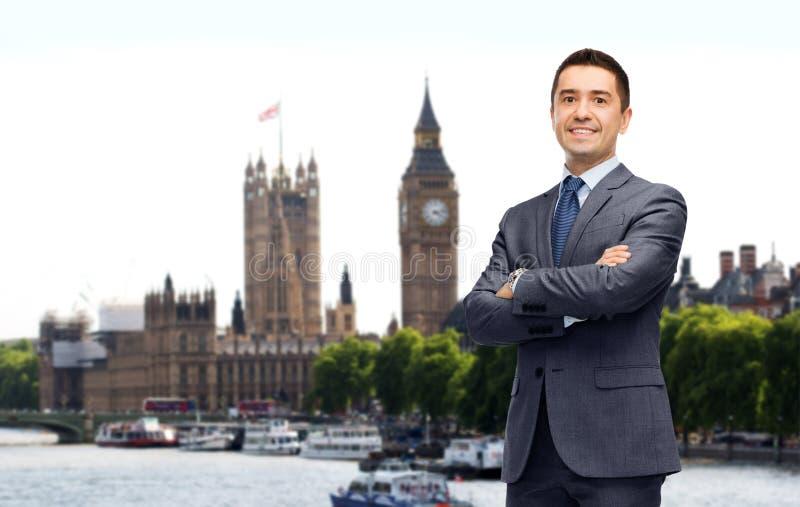 Homem de negócios de sorriso feliz no terno sobre a cidade de Londres fotos de stock royalty free